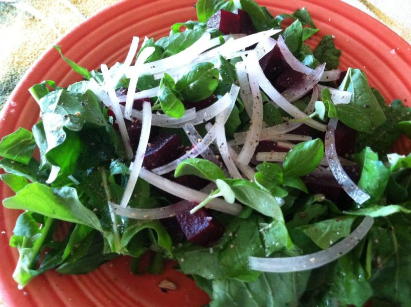 Closeup of arugula salad with basil trimmings