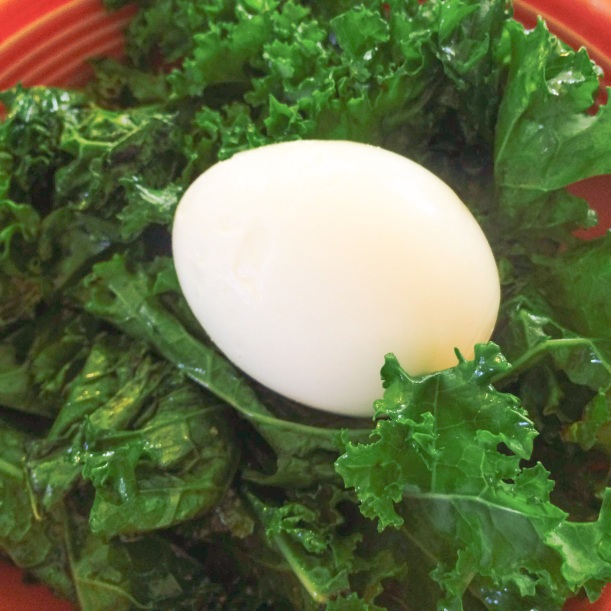Soft boiled egg on sautéed kale